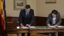 PSOE leader and Acting Prime Minister Pedro Sánchez and Podemos leader Pablo Iglesias signing a preliminary agreement last Tuesday to form a coalition government.